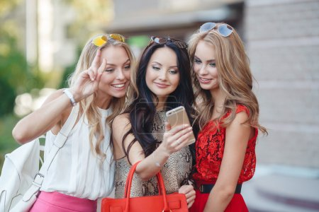 Photo pour Trois jeunes belles femmes, deux blondes et une brune, font une promenade ensemble en ville en été, en regardant des photos sur votre Smartphone en levant sur les lunettes de soleil du front - image libre de droit