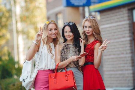 Photo pour Trois petites amies heureuses, deux blondes et la brune, en lunettes de soleil, sont vêtues de robes d'été faciles, avec des sacs dans les mains, se rendent dans un supermarché pour faire du shopping, sourire et poser pour le photographe - image libre de droit