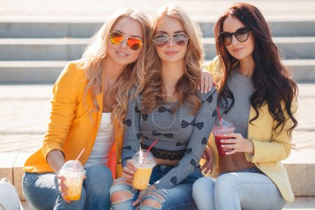 Photo pour Trois belles jeunes femmes, deux blondes et une brune, marchent ensemble dans le parc en été, assises sur les marches, buvant du jus de fruits et portant des lunettes de soleil - image libre de droit