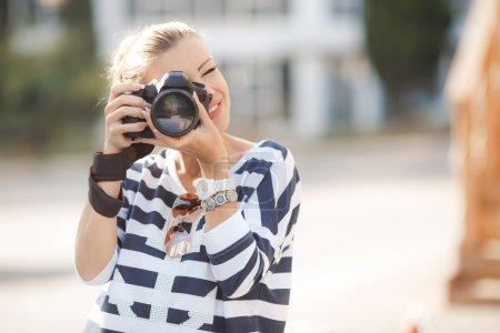 Photo pour Jeune femme brune en chemisier rayé, beau maquillage, avec un appareil photo numérique professionnel, fait ce qu'il aime la photographie en été en plein air, voyageant en Europe - image libre de droit