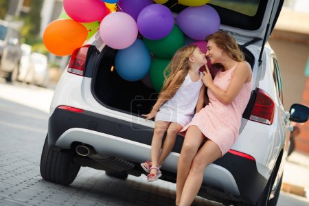 Photo for Happy family,mother is a brunette with long curly hair and brown eyes,dressed in a pink dress and little daughter girl, brunette,dressed in a white dress ,spend time together,sitting in the trunk of a white car with colorful balloons - Royalty Free Image