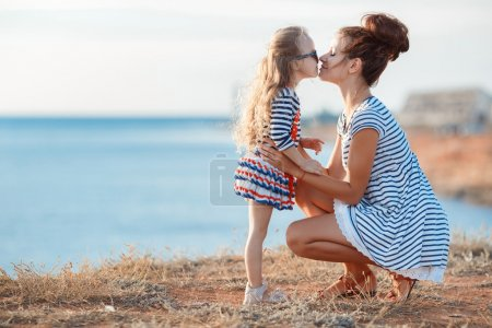 Mother and his adorable little daughter at beach