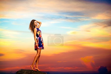 Young woman in summer dress standing on a rock