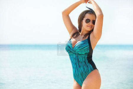 Overweight young woman in swimsuit near the sea. Size plus