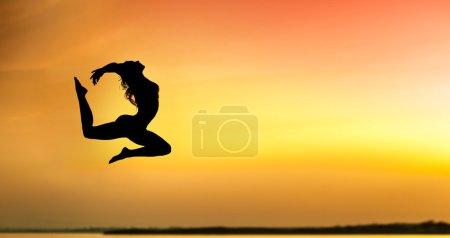Photo pour Femme sport saut contre le beau coucher de soleil. Liberté, la notion de plaisir - image libre de droit