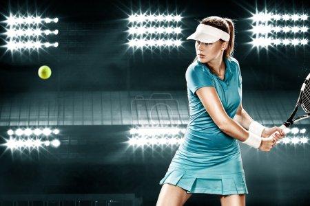 Photo pour Joueuse de tennis belle fille avec une raquette sur fond sombre avec des lumières - image libre de droit