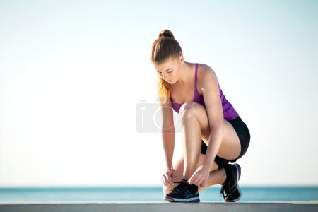 Girl jogger sitting and lacing up her running shoes