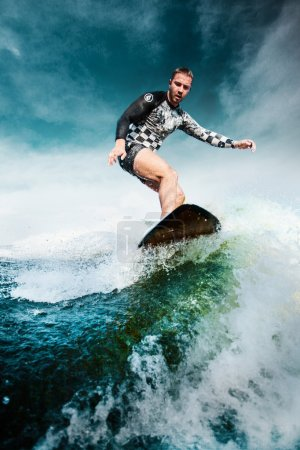 Surfing at blue ocean. Young man balanced on kiteboard, wakeboard.