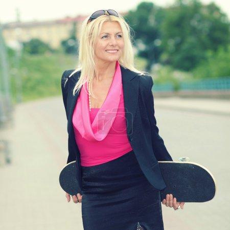 Photo pour Femme d'affaires senior avec une planche à roulettes à l'extérieur - image libre de droit