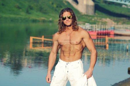 Photo pour Beau modèle de remise en forme homme torse nu marche le long de la plage dans la ville. tonique . - image libre de droit