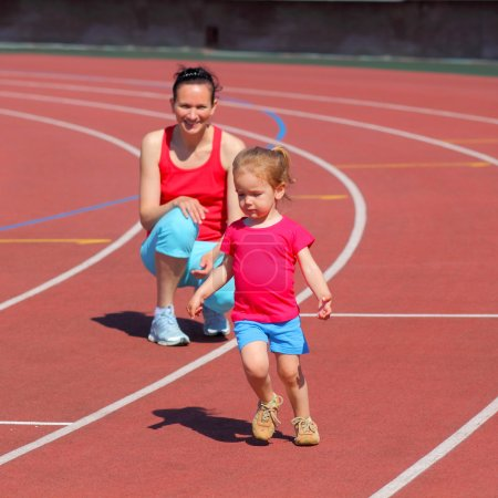 Mother and daughter exercising at stadium