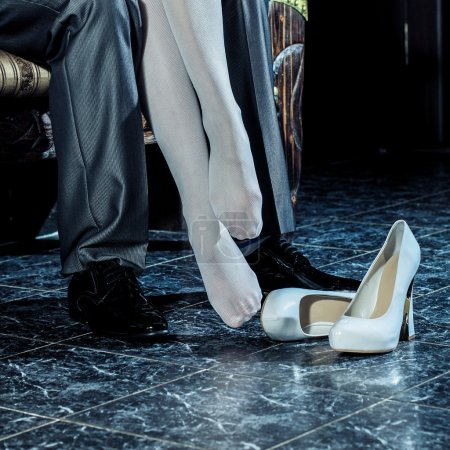 Photo for Girl in white stockings seduces man indoors. Embrace the man and woman in a restaurant - Royalty Free Image