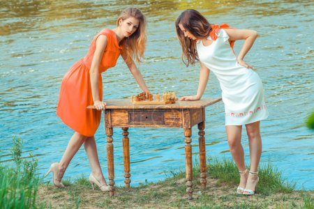 girls in a dress playing chess