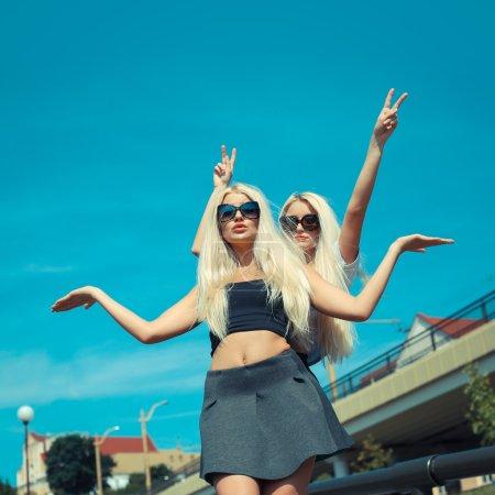 two cheerful blonde girlfriends