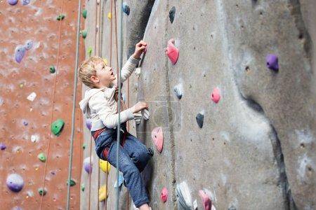 Foto de Determinado poco chico disfrutando de escalada en roca en el gimnasio de escalada interior, concepto de estilo de vida saludable y activa - Imagen libre de derechos