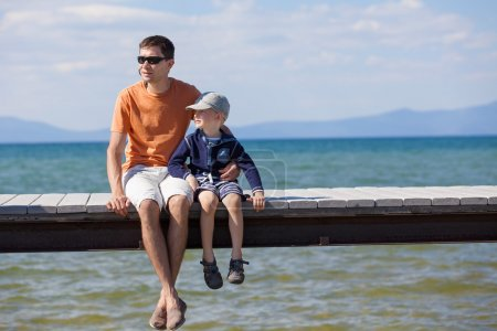 Photo for Cheerful family of two sitting at the dock during vacation at lake tahoe, california, usa - Royalty Free Image