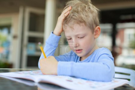 Photo for Concentrated little boy doing homework - Royalty Free Image