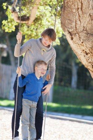 Foto de Hermosa joven madre y su pequeño hijo disfrutando de tiempo juntos y divirtiéndose en el parque balanceándose - Imagen libre de derechos