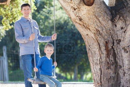Foto de Guapo padre joven y su pequeño hijo disfrutando de tiempo juntos y divirtiéndose en el parque balanceándose - Imagen libre de derechos