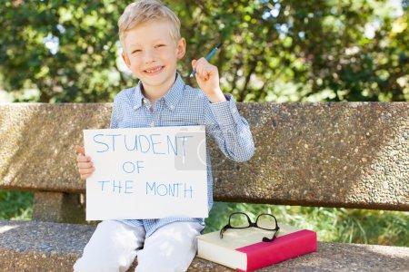Photo pour Sourire garçon tenant étudiant du mois signe prêt pour l'année scolaire - image libre de droit