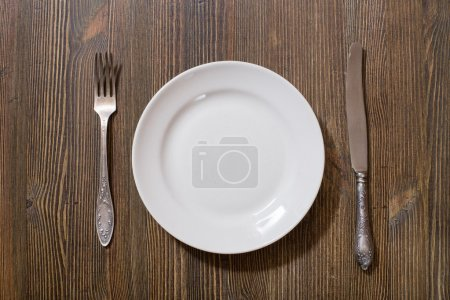 Photo for Antique fork, knife and plate on wooden table - Royalty Free Image