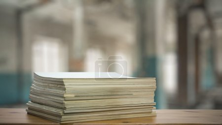 Stack of old magazines on wooden table with blurre...