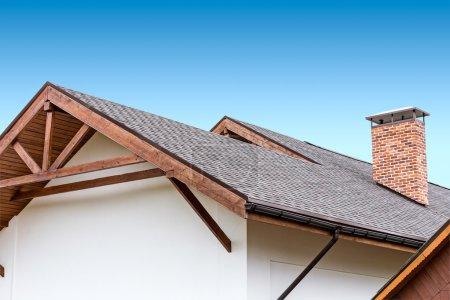 Photo pour Maison neuve avec botte de bois de toit lourd - image libre de droit