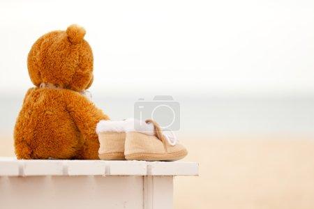 Photo pour L'ours en peluche solitaire et les bottines de bébé restent sur un transat sur la plage de l'océan. Concept sur l'enfance, la solitude et l'espérance - image libre de droit