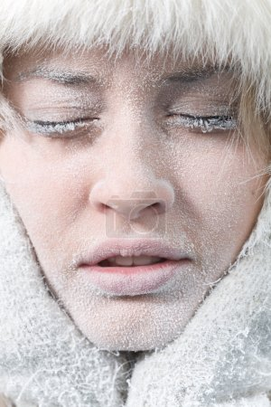 Very cold weather. Chilled female face covered in ice.