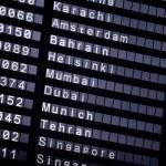 A flight schedule at the airport show Karachi, Ams...