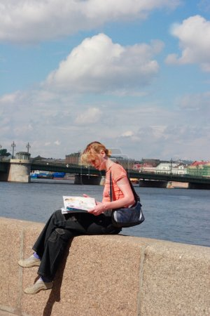 Girl reading magazine on canal border in Saint Petersburg