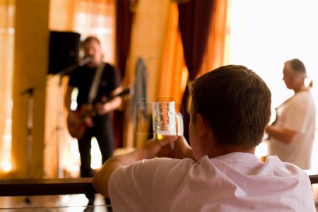 Man having beer and  look on playing band