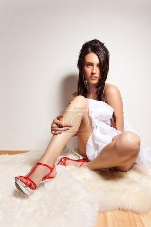 Attrayant nu fille assise sur le sol en bois et couvrir votre corps