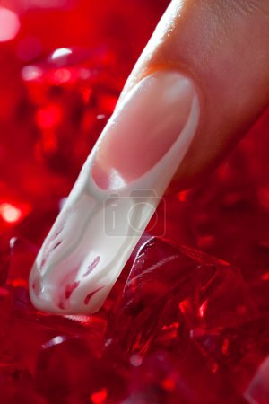 Finger with beautiful manicure touch a red crystal