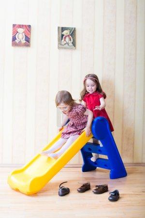 Photo pour Deux adorables filles s'amusent sur le toboggan de l'aire de jeux au salon - image libre de droit