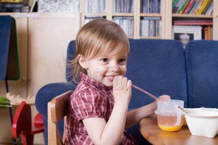 Little girl drinking fresh orange juice and smile