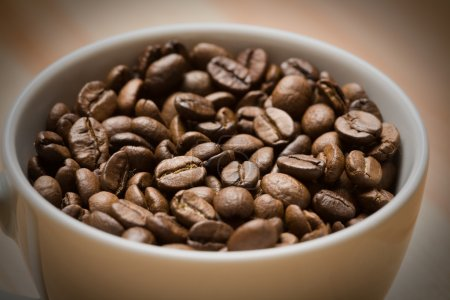 Cup with freshly roasted coffee beans