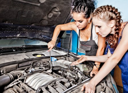 Two female auto mechanic repairing a car
