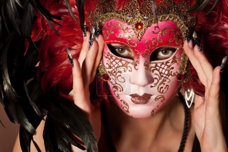 Woman with beautiful manicure on long finger hold venetian mask