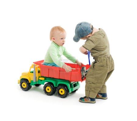 Dos niños pequeños juegan con camión de juguete