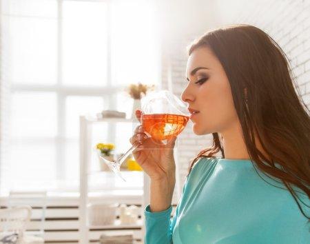 Photo pour Belle femme dégustant un verre de vin rose . - image libre de droit