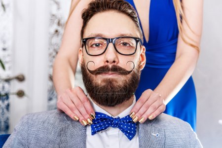 Photo pour Femme avec manucure redresse un noeud papillon à l'homme à l'ancienne dans des lunettes avec une barbe et une moustache frisée. Photo tonique en sépia, tige rétro stylisée . - image libre de droit