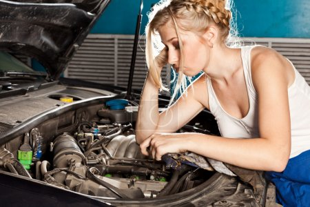 Girl tries to repair broken car