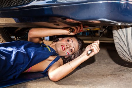 Woman checks the suspension of the car in service.