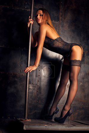 Photo for Young slim sexy pole dance woman in black lingerie on dark metallic wall background. - Royalty Free Image
