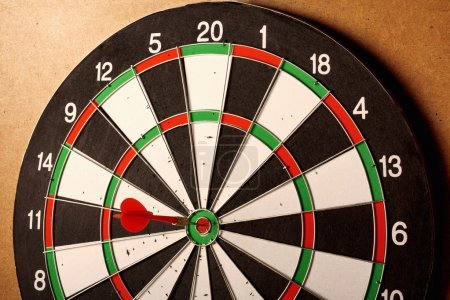 Vintage dart board on dark wall