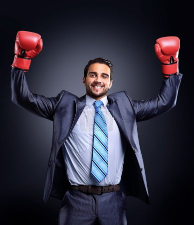 Businessman in a suit and boxing gloves