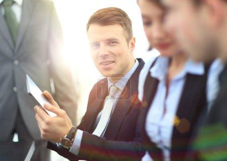 Photo pour Homme d'affaires posant dans la salle de réunion, alors que les collègues travaillent derrière - image libre de droit