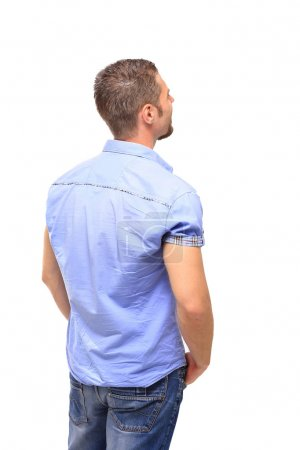 Young man from the back - looking at something over a white back