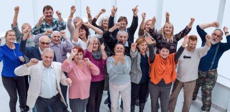 groupe d'amis matures levé les mains et célébrer succ